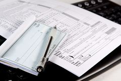 Preparing Taxes - Check and Forms on Keyboard Stock Photos