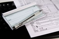 Preparing Taxes - Check and Forms on Keyboard Royalty Free Stock Photos