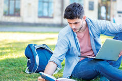 Preparing for tests. Cute male student holding a laptop and read Royalty Free Stock Image