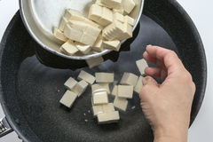 Preparing to boil fresh tofu in black pan in the kitchen. Deliciously stock image