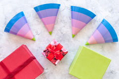 Preparing to celebration. Colored gift boxes and party hats on grey stone background top view Stock Image