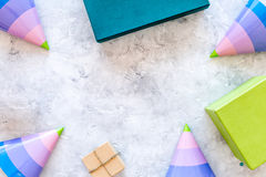 Preparing to celebration. Colored gift boxes and party hats on grey stone background top view copyspace Stock Images