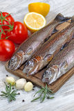 Preparing to Cook Wild Trout. Vertical image of fresh wild trout being prepared, skin coated with oil, for cooking on server board. Herbs, tomatoes, lemon and Stock Images