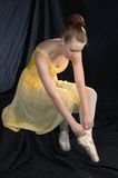Preparing to Dance. A ballerina ties the ribbon on her shoe preparing for dance Stock Photo
