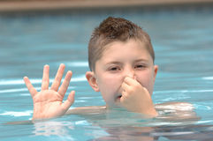 Preparing to dive. A young boy waves and uses his other hand to hold his nose, preparing to dive underwater in a swimming pool royalty free stock photography