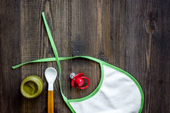 Preparing to feed baby. Puree, spoon, nipple and bib on dark wooden table background top view copyspace Stock Photos