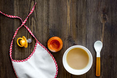 Preparing to feed baby. Puree, spoon, nipple and bib on dark wooden table background top view copyspace Stock Images