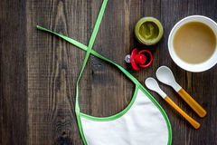 Preparing to feed baby. Puree, spoon, nipple and bib on dark wooden table background top view copyspace Royalty Free Stock Images
