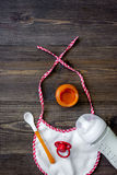 Preparing to feed baby. Puree, spoon, nipple, bottle and bib on dark wooden table background top view copyspace Royalty Free Stock Photo