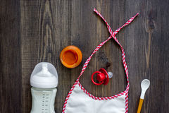 Preparing to feed baby. Puree, spoon, nipple, bottle and bib on dark wooden table background top view copyspace Royalty Free Stock Photography