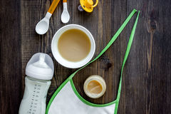 Preparing to feed baby. Puree, spoon, nipple, bottle and bib on dark wooden table background top view copyspace Royalty Free Stock Image