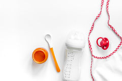 Preparing to feed baby. Puree, spoon, nipple, bottle and bib on white background top view copyspace Royalty Free Stock Image