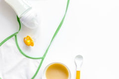 Preparing to feed baby. Puree, spoon, nipple, bottle and bib on white background top view copyspace Stock Photography