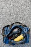 Sports bag and boxing gloves with water at the asphalt background royalty free stock images