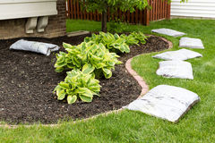 Preparing to mulch the garden in spring. Laying out a row of commercial organic mulch in bags around the edge of the flowerbed on a neatly manicured green lawn Royalty Free Stock Image