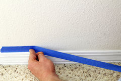 Preparing to Paint. Male hand preparing to paint wall trim by placing blue painter's tape on the wall above it for protection stock photos