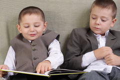 Preparing to school. Elder brother supervise after younger boy reading Stock Image