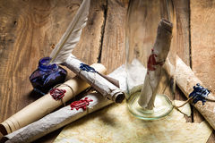 Preparing to send ancient letter in a bottle with blue ink. On old wooden table Royalty Free Stock Photography