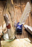 Preparing to send ancient letter in a bottle and writting with b. Lue ink on old woodne table Royalty Free Stock Image