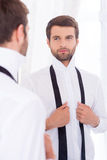 Preparing to a special day. Handsome young man in white shirt and untied necktie standing against mirror Stock Photo
