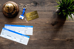 Preparing to trip. Book hotel and tickets. Tickets near service bell, bank card on dark wooden table top view copyspace Stock Images