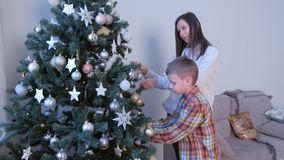 Mom and son decorating artificial Christmas tree in living room at home together. stock video