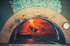 Preparing traditional italian pizza. Food concept. Preparing traditional italian pizza. Long shovel for pizza, baking dough in a professional oven with open Stock Image