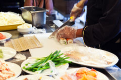 Preparing of traditional Japanese sushi, cutting. Preparing of traditional Japanese sushi with salmon, cook cuts roll of rice and fish. Selective focus Stock Photo