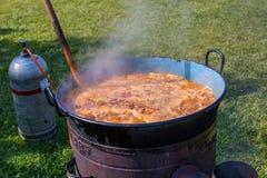 Preparing traditional Ukrainian soup borscht in a large metal pot on gas campfire outdoor stock photo