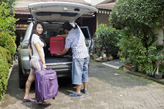 Preparing for travel. Smiling asian women with her husband loading baggage in car, preparing for travel Royalty Free Stock Photos