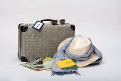 Preparing for Travel. Preparing for a journey. Vintage suitcase with a map, travel documents, a hat, money and sunglasses, displayed on a white background Royalty Free Stock Photo