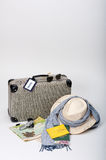 Preparing for Travel. Preparing for a journey. Vintage suitcase with a map, travel documents, a hat, money and sunglasses, displayed on a white background Stock Photos