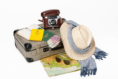 Preparing for Travel. Preparing for a journey. Vintage suitcase with a map, travel documents, a hat, money and sunglasses, displayed on a white background Royalty Free Stock Image