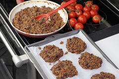 Preparing Tricolor Bean Quinoa Burgers. Parchment paper lined cookie sheet with quinoa and three bean patties ready to be cooked. Preparing tricolor bean and royalty free stock images