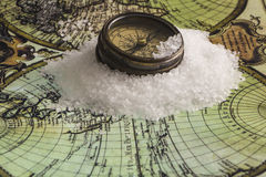 Preparing for the trip. Antique compass on white ice floes on a world map background stock images