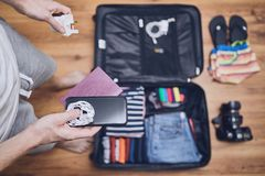 Preparing for trip. Young man packing clothing for vacation, flip flop, camera and other things on hardwood floor royalty free stock photos