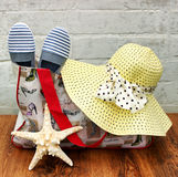 Preparing for the trip. Straw hat, beach bag and slippers,  sea shell star close-up on the wooden floor Royalty Free Stock Image