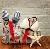 Preparing for the trip. Swimsuit, beach bag and slippers,  sea shell star close-up on the wooden floor Stock Photography