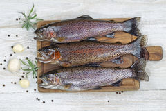 Preparing Trout for Dinner. Top view of fresh trout being prepared, skin coated with oil, for cooking on server board. Herbs and spices on white aged wooden Royalty Free Stock Photo