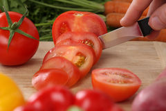 Preparing vegetables food sliced tomato on a kitchen board Royalty Free Stock Images