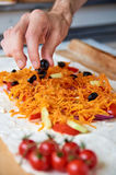 Preparing vegetarian burrito with vegetables and olives. Hand with black olive. On blurred foreground cherry tomatoes Royalty Free Stock Image