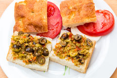 Preparing vegetarian sandwiches with pickle muffaletta, tomatoes Stock Image