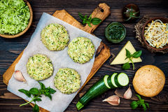 Preparing veggies cutlets or patties for burgers. Zucchini quinoa veggie burger with pesto sauce and sprouts. Top view, overhead Royalty Free Stock Photography