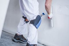 Preparing Wall For Painting. Drywall Patching by Caucasian Construction Worker Royalty Free Stock Photography