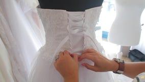 Preparing a wedding dress for a wedding. Fashion designer prepares a wedding dress for the bride stock video