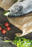 Preparing whole salmon fish for cooking. Vegetables on the table. Vintage style Stock Photos