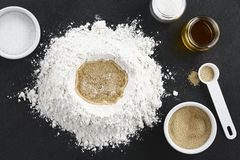 Preparing Yeast Dough. For bread or pizza baking, photographed overhead on slate royalty free stock photos