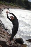 prepearing的多岩石的海滩的年轻运动员游泳 免版税库存图片