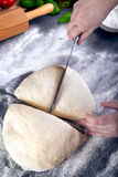 Prepering and cutting pizza dough with knife Stock Images