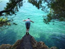 Preraparing for jump. Man preparing to jump in the Adriatic sea from the rock Royalty Free Stock Photo